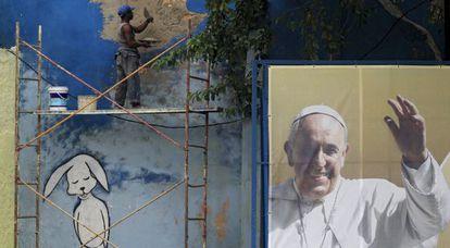 Um operário conserta um muro junto a um cartaz do Papa.