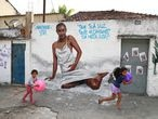 Girls play with balls in front of the graffiti made by artists in honor of Kathlen de Oliveira Romeu, who was pregnant and was shot dead during a police operation, according to local media, at the Lins slums complex in Rio de Janeiro, Brazil June 14, 2021. REUTERS/Pilar Olivares