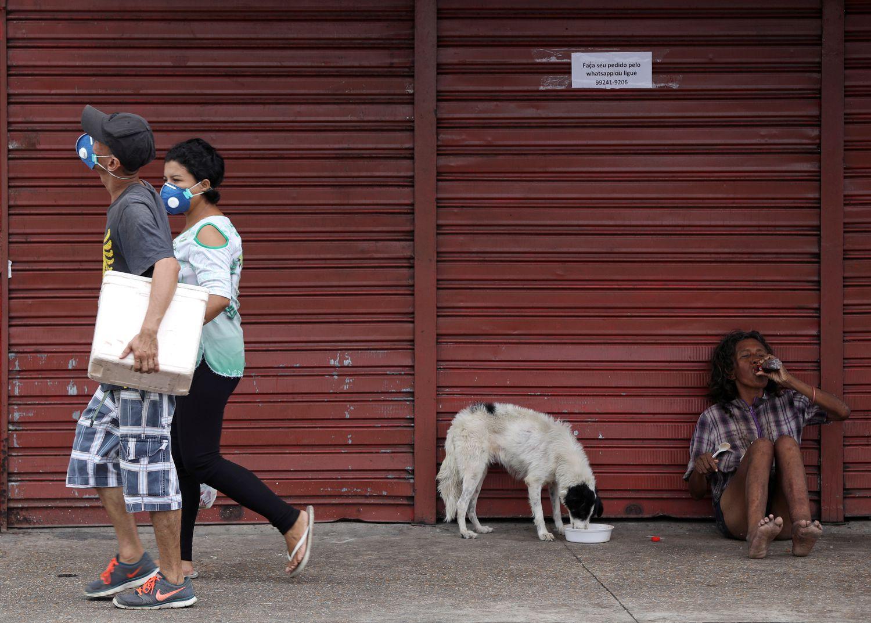 Pessoas com máscaras protetoras andam durante o surto de doença de coronavírus, perto do Porto de Manaus.