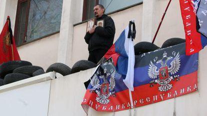 Um ativista pró-Rússia reza na varanda do edifício do governo de Mariupol.