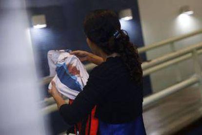 Bruna, mãe do adolescente Marcos Vinicius da Silva, segura camisa da escola que o estudante usava.