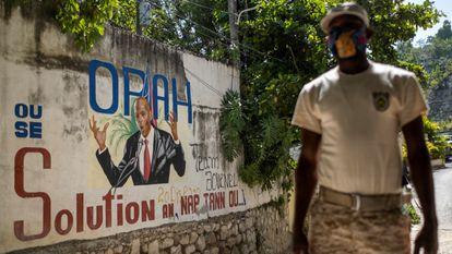 Policial monta guarda em 11 de julho diante de um mural que mostra o presidente haitiano Jovenel Moise na entrada da casa onde foi assassinado, em Porto Príncipe.