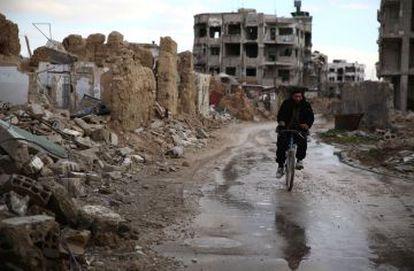 Um sírio anda de bicicleta no bairro de Hazeh, região leste da capital, Damasco.