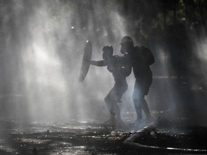 Manifestantes se defendem dos jatos d'água com os quais a polícia tenta dispersá-los, durante um protesto em Santiago.