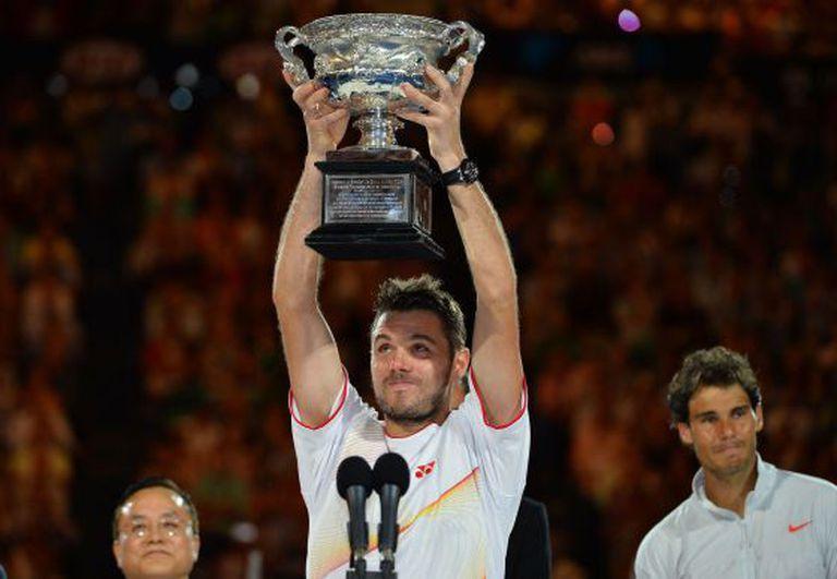 Wawrinka levanta o troféu. Atrás dele, Nadal.
