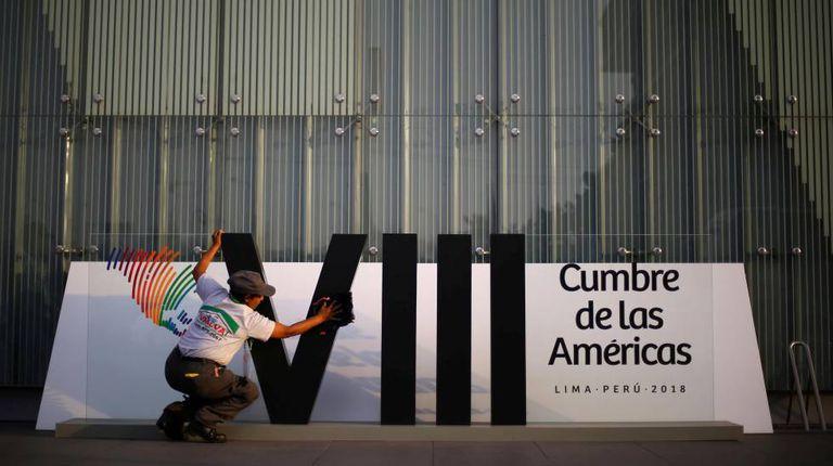 Mulher limpa o logotipo da Cúpula das Américas em Lima