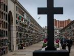 A woman and her brother walk through the Poble Nou cemetery in Barcelona, Spain, Saturday, April 18, 2020, after attending the funeral of their mother who died of coronavirus. (AP Photo/Emilio Morenatti)