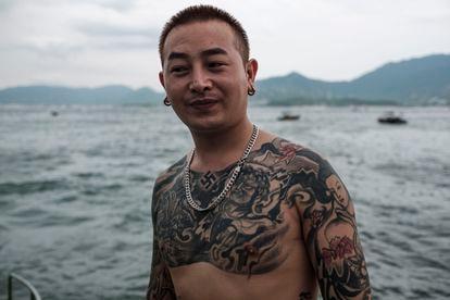 Um chinês tatuado posa para a foto, na praia de Dapeng Jiaochangwei.
