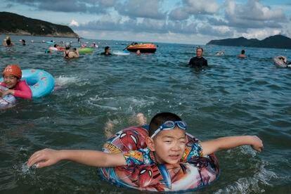 Uma criança nada com a ajuda de uma boia na praia de Dongchong.