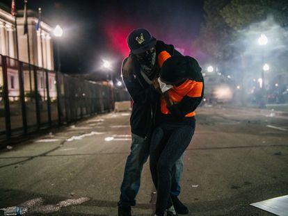 Homem socorre manifestante em Kenosha, Wisconsin, na terceira noite de protestos contra ação policial.