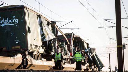 Vários operários passam junto ao trem de carga na ponte do Grande Belt, em Nyborg (Dinamarca).