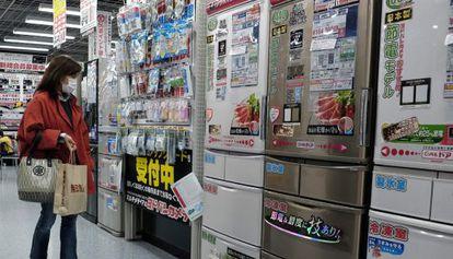 Uma mulher observa refrigeradores em uma loja de Tóquio.
