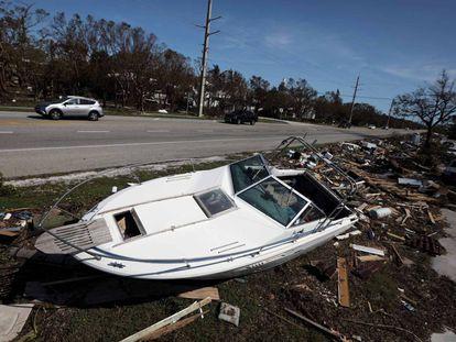 Barco ao lado de destroços causados pelo Irma em uma estrada na Flórida.