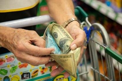 O professor aposentado manuseia sua carteira enquanto faz compras.