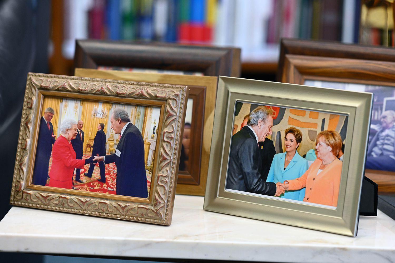 Fotografias do ministro Ricardo Lewandowski com a rainha Elizabeth II (à esquerda) e com Angela Merkel e Dilma Rousseff expostas em seu gabinete.