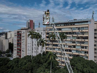 """Bombeiro toca trompete para os vizinhos confinados no bairro de Laranjeiras, no Rio de Janeiro. No vídeo, sua interpretação do """"Samba do Avião""""."""
