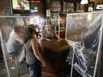 Sheila Kelly, owner of Powell's Steamer Co. & Pub, center, stands behind makeshift barriers as she helps patrons at her restaurant in the El Dorado County town of Placerville, Calif., Wednesday, May 13, 2020. It was the first day Kelly was serving in-dining meals since the state's lockdown order to slow the spread of the coronavirus. El Dorado County was one of the first counties to win approval from the state to reopen for dining-in. (AP Photo/Rich Pedroncelli)