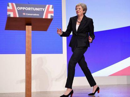 May entra dançando no palco pouco antes de seu dicurso.