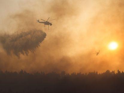 Um helicóptero joga água sobre o incêndio na região de Varimpompi, ao norte de Atenas.