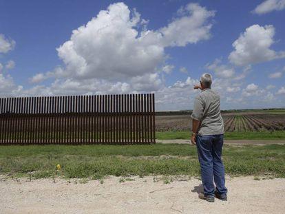 Homem aponta para trecho de cerca na fronteira em Brownsville (Texas), em uma imagem de 2005