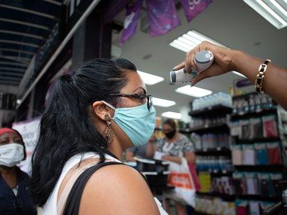Uma vendedora mede a temperatura de uma cliente antes de ela entrar em uma loja de São Paulo.