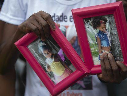 Ana Lúcia Silva Moreira, mãe de Emily Victória, 4, segura as fotos da filha e de sua sobrinha, Rebeca Beatriz, 7, mortas pela polícia.