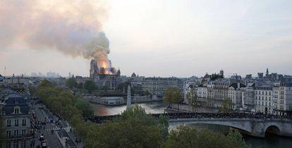 Centenas de pessoas contemplam o avanço das chamas em uma ponte sobre o Sena.