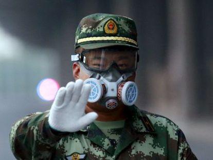 Um policial para a um fotógrafo que pretendia aceder à zona que foi evacuada em Tianjin, nesta segunda-feira.