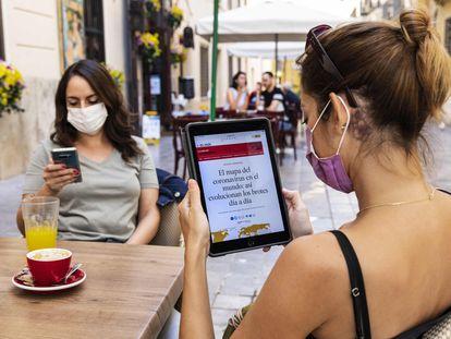 Uma leitora consulta o EL PAÍS em seu tablet em um terraço de Valência.