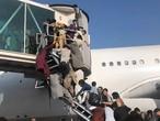 Afganos intentan acceder a un avión en el aeropuerto de Kabul, este lunes.