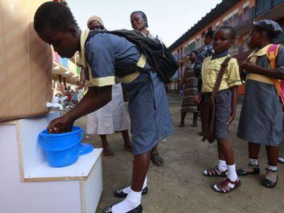 Niñas lavam-se as mãos em um colégio em Lagos, Nigeria