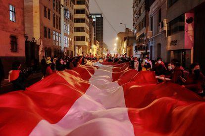 Bandeira do Peru nas mãos de seguidores do candidato Pedro Castillo no centro de Lima, nesta segunda-feira.