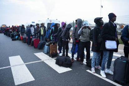 Fila de refugiados esperando ser evacuados do acampamento de Calais, em outubro de 2016.