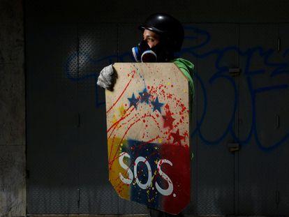 """Manifestante ergue um escudo rudimentar, ao posar para um retrato antes de um protesto contra o Governo do presidente Nicolás Maduro, em Caracas, em 27 de maio de 2017. 'Protesto pela liberdade. Quero saber que posso estudar e aspirar a algo melhor. O regime nos roubou tudo, a qualidade de vida e as oportunidades""""."""