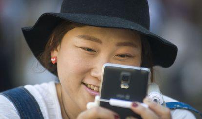 Uma turista asiática olha seu telefone celular.