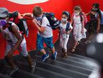 Students with face masks go upstairs to their classrooms at the Petri primary school in Dortmund, western Germany, on August 12, 2020, amid the novel coronavirus COVID-19 pandemic. - Schools in the western federal state of North Rhine-Westphalia re-started under strict health guidelines after the summer holidays. (Photo by Ina FASSBENDER / AFP)