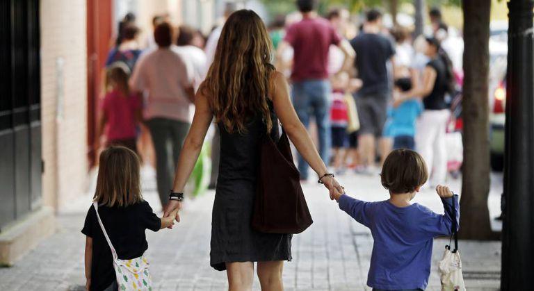 Uma mãe leva a seus filhos ao colégio.