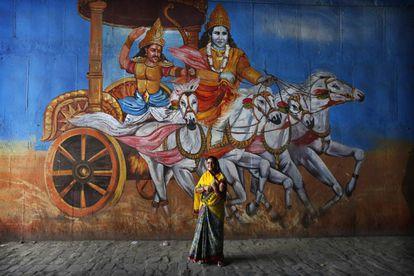 Uma eleitora, diante de um mural com uma cena do Mahabharata, em Uttar Pradesh.