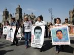 Relatives of the 43 missing students of Ayotzinapa College Raul Isidro Burgos hold banners with photos of their loved ones while leaving the National Palace after a meeting with government officials, in Mexico City, Mexico January 9, 2020. REUTERS/Luis Cortes