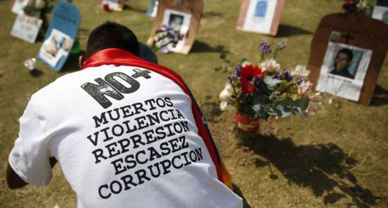 Uma pessoa diante do túmulo de mortos por violência na Venezuela
