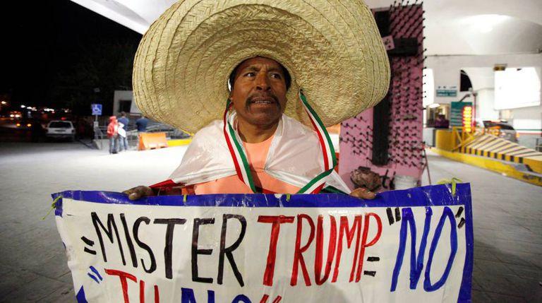 Martin Macias segura cartaz contra Trump em Ciudad Juarez, no México.