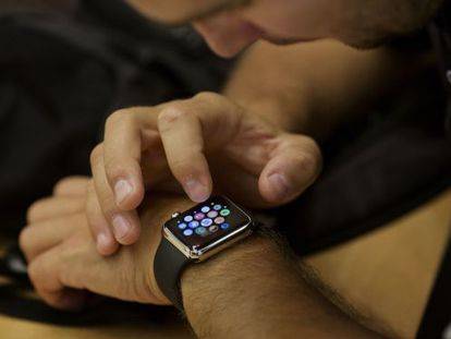 """An employee sets up an Apple Watch for a customer at an Apple Inc. store, in New York, U.S., on Wednesday, June 17, 2015. Apple Inc. is rolling out a """"Reserve & Pickup"""" system which allows customers to choose a Watch online then buy and collect the order in store. Photographer: Victor J. Blue/Bloomberg"""