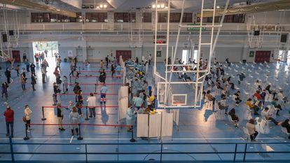 Trabalhadores da Saúde administram a vacina da AstraZeneca no ginásio de esportes da Universidade de Sevilha.
