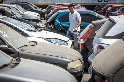 Consumidor analisa carros em pátio de leilão público em Guarulhos.