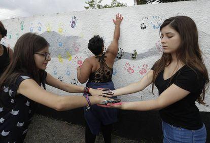 Alunas colocam suas impressões digitais em uma parede na Escola Estadual Raul Brasil, palco de um massacre praticado por dois ex-alunos.