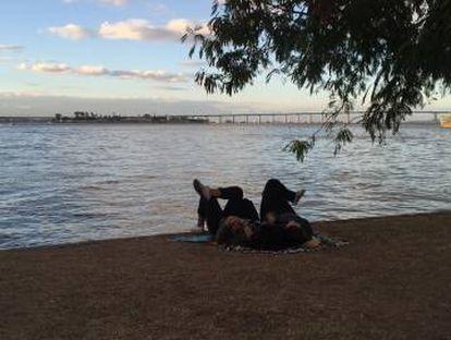 Duas pessoas descansam no gramado do porto.