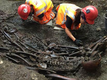 Dois arqueólogos escavam uma vala comum com vítimas da peste em Londres.