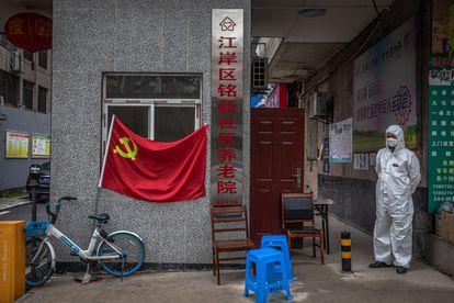 Homem com traje protetor numa rua da cidade chinesa de Wuhan, nesta segunda-feira.
