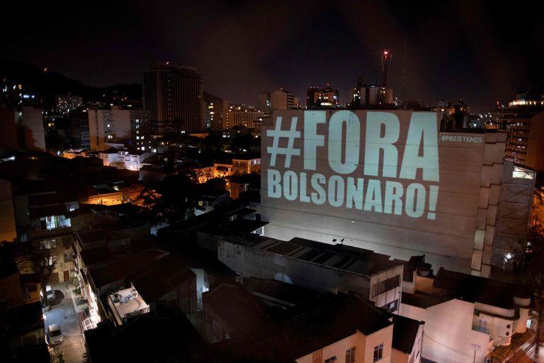 Projeção no bairro de Botafogo, no Rio, homenageia vítimas da covid-19 e pede a saída de Bolsonaro.
