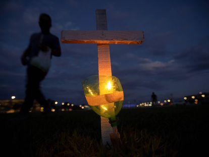 Integrantes de diversos movimientos sociales realizan un acto en el que encienden velas pegadas a 400 cruces, en frente al edificio del Congreso Nacional, como homenaje a las 395.000 muertes por covid-19 que acumula Brasil desde el comienzo de la crisis sanitaria, hace poco más de un año.